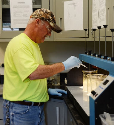 Steve Nelson, industrial waste water operator, Industrial Waste Treatment Plant, Public Works, Installation and Environment Division, adds treatment chemicals during a jar test at the IWTP's lab. A jar test is conducted every shift to make sure the plant is operating correctly.