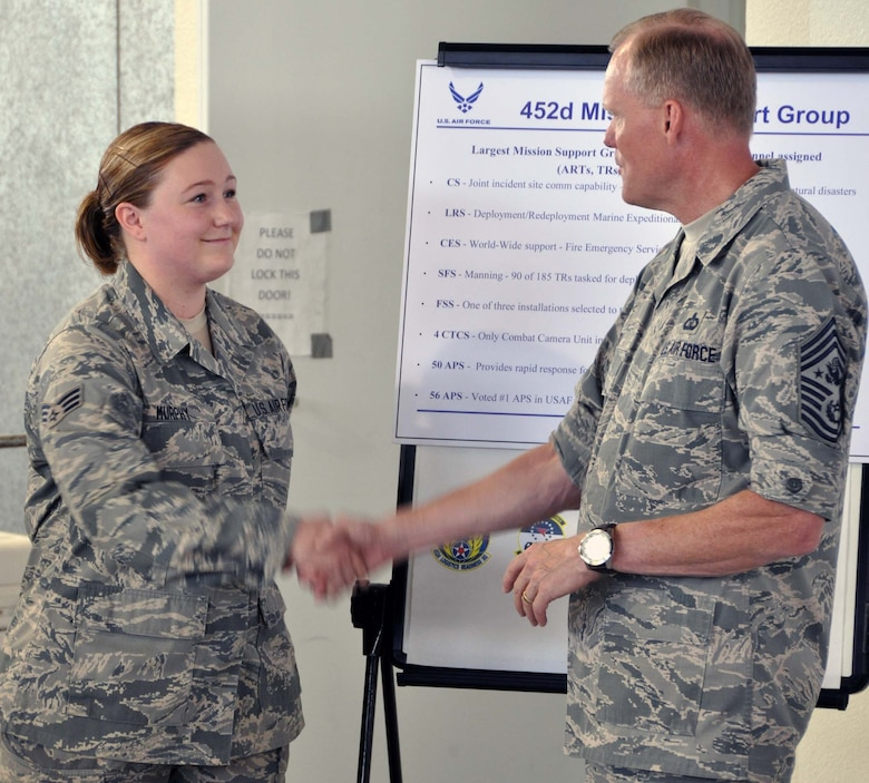 Chief Master Sgt of the Air Force James A. Cody presented his coin to Senior Airman Aubrey Murphy, 56th Aerial Port Squadron, to thank her for doing so well in her explanation of the Mission Support Group's overall mission. CMSAF Cody and Athena visited March Air Reserve Base in Southern California July 11-14, 2014, where they met with Airmen and observed the success of Total Force Integration there. (U.S. Air Force photo/Master Sgt. Linda Welz)
