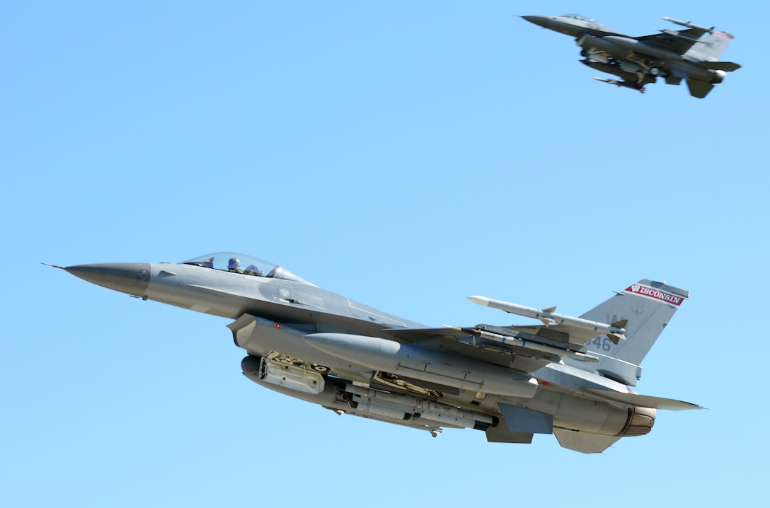 Two F-16 Fighting Falcons from the 115th Fighter Wing in Madison, Wis., perform flyover maneuvers prior to landing on the runway at Volk Field Air National Guard Base, Wis., July 16, 2014. The jets were moved to Volk Field for the month of July, while the Dane County Regional Airport completed runway maintenance and repairs. (Air National Guard photo by Senior Airman Andrea F. Liechti)
