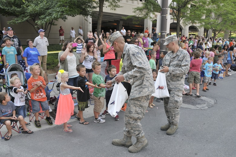 Air Guard members from the 122nd Fighter Wing, Fort Wayne, Indiana hand out candy to spectating children during the 46th Annual Three Rivers Festival Parade, July 12, 2014, held on the streets of downtown Fort Wayne. The yearly parade, attended by approximately 50,000 people, allows the wing to show its community support. (Air National Guard photo by Airman 1st Class Justin Andras/Released)