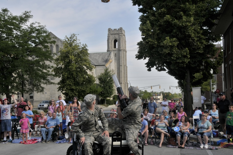 Air Guard members from the 122nd Fighter Wing, Fort Wayne, Indiana shoot T-shirts into the crowd at the 46th Annual Three Rivers Festival Parade, July 12, 2014, in the streets of downtown Fort Wayne. The yearly parade, attended by approximately 50,000 people, allows the wing to show its community support. (Air National Guard photo by Airman 1st Class Justin Andras/Released)