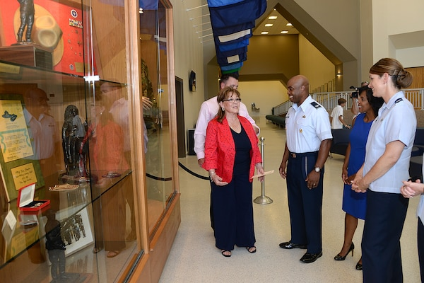 Marsha Pfingston (left) talks to Col. Trent Edwards, 37th Training commander; Edwards' wife Vanessa; and Col. Michele Edmondson, 737th Training Group commander, about the exhibit in the new Recruit/Family In-processing and Information Center at Joint Base San Antonio-Lackland, Texas July 30, 2014 that honors her late husband, 10th Chief Master Sergeant of the Air Force Gary Pfingston. (U.S. Air Force Photo by Benjamin Faske/Released)