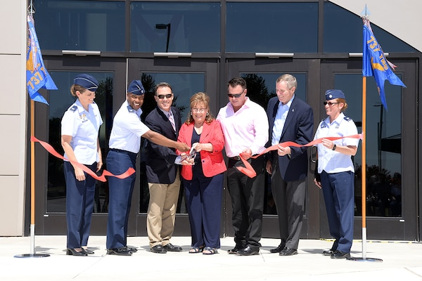 Marsha Pfingston (center) cuts the ribbon to the new Recruit/Family In-processing and Information Center at Joint Base San Antonio-Lackland, Texas July 30, 2014 that was named after her late husband, 10th Chief Master Sergeant of the Air Force Gary Pfingston. Assisting her, from left, were Col. Michele Edmondson, 737th Training Group commander; Col. Trent Edwards, 37th Training Wing commander; her sons, Mark and Brad Pfingston;12th CMSAF Eric Benken; and Lt. Col. Jill Murphy, 737th Training Support Squadron commander. (U.S. Air Force Photo by Benjamin Faske/Released)
