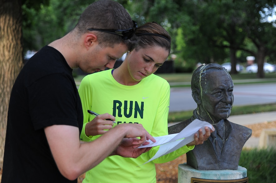 Scavenger hunt participants reread a clue at Scott Air Force Base, Ill., July 25, 2014. The clue asked them to review the information on the busts in front of the 375th Air Mobility Wing headquarters. They had to determine which three busts, representing three former Team Scott members, matched the clues provided. (U.S. Air Force photo/Staff Sgt. Jonathan Fowler)