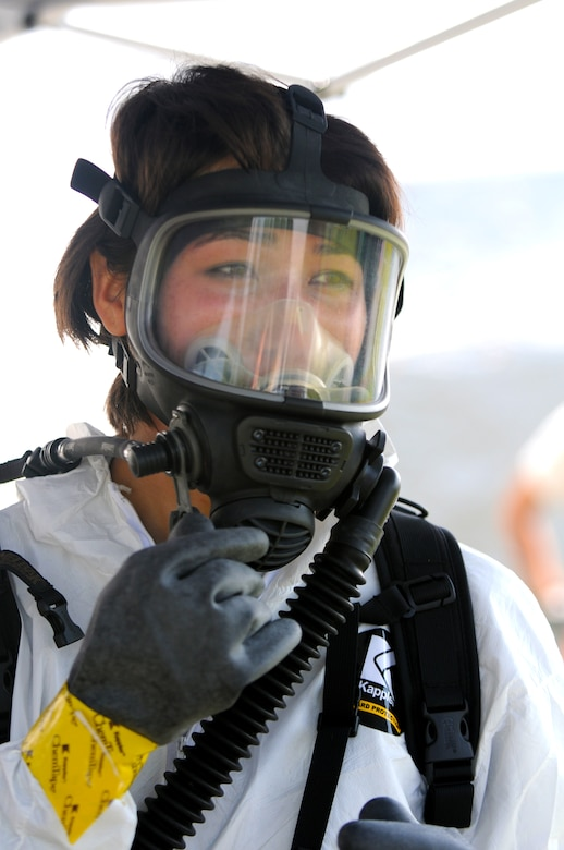 U.S. Air Force Staff Sgt. Sara Ingle dons her gas mask in preparation for performing triage duties during exercise Vibrant Response July 22, 2014 at Camp Atterbury, Ind. Staff Sgt. Ingle is part of the CBRNE Enhanced Response Force Packages Team (CERF-P). (U.S. Air National Guard photo by Master Sgt. Ralph Branson/Released)