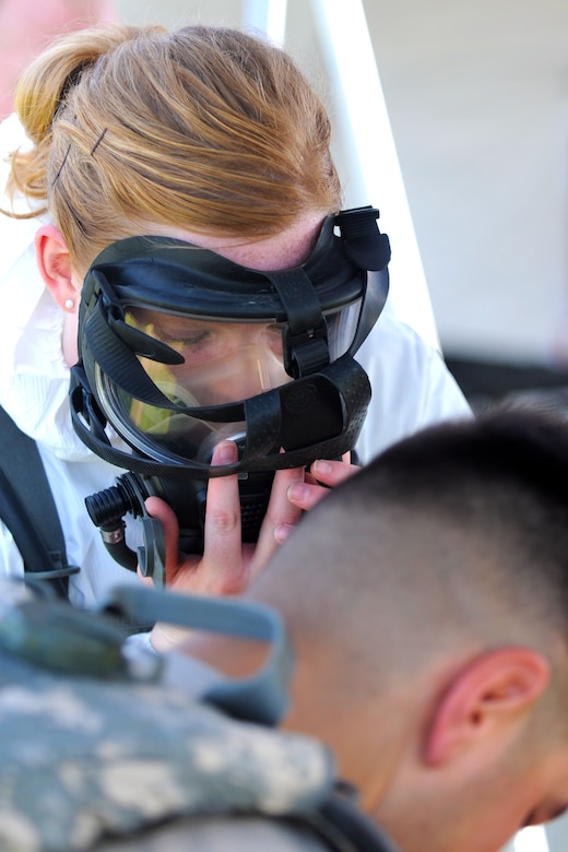 U.S. Air Force Airman 1st Class Sarah Poquette dons her gas mask in preparation for performing triage duties during Joint Exercise Vibrant Response July 22, 2014 at Camp Atterbury, Ind. Airman 1st Class Poquette, 121st Air Refueling Wing medical group, is part of the CBRNE Enhanced Response Force Packages Team.  (CERF-P). (U.S. Air National Guard photo by Master Sgt. Ralph Branson/Released)