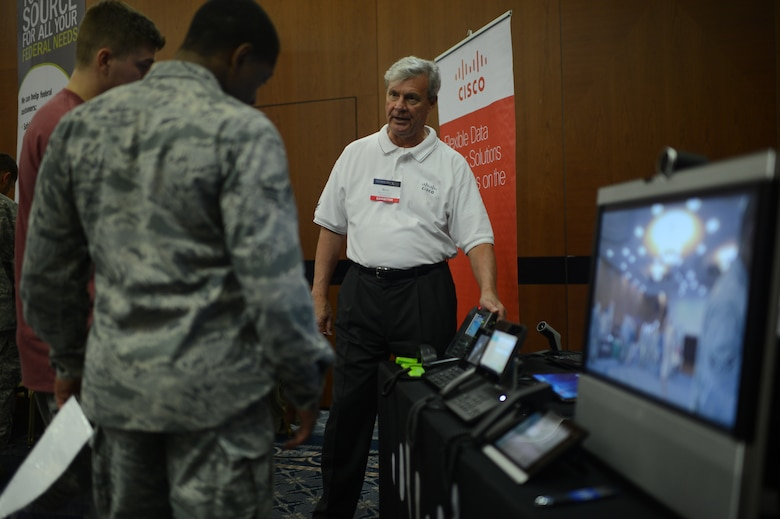Rick Ottinger, Cisco systems exhibitor, demonstrates new conference-call capabilities at the 2014 Spangdahlem Technology Expo at Club Eifel, July 30, 2014. The display included multiple ways to connect video devices to phone systems for face-to-face real-time interaction. (U.S. Air Force photo by Senior Airman Gustavo Castillo/Released)