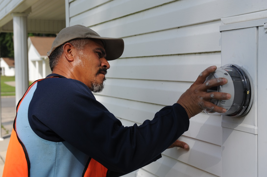 Lazaro Sierra, Sierra Enterprises owner, installs an electric meter to an on-base house July 23, 2014, at Seymour Johnson Air Force Base, North Carolina. Sierra and other workers installed meters on more than 600 on-base houses. (U.S. Air Force photo/Airman 1st Class Aaron J. Jenne)
