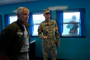 Defense Secretary Chuck Hagel, left, receives a briefing as a North Korean soldier takes pictures of him through a window at Freedom House and Conference Row in Korea's Demilitarized Zone, Sept. 30, 2013. DOD photo by Erin A. Kirk-Cuomo