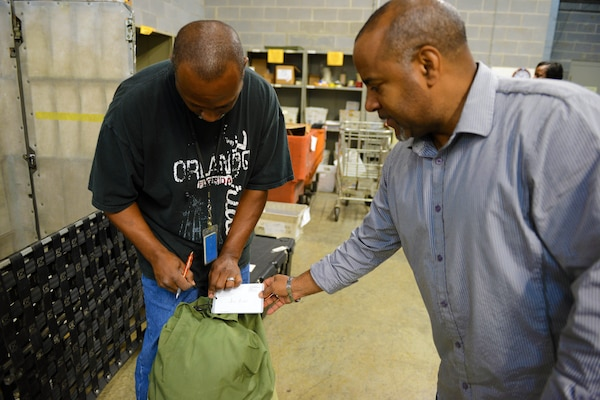 Dyrick Fowler, a clerk in the military section of the U.S. Postal Service's Mail Recovery Center in Atlanta, and Lionel Snow, the center's manager, demonstrate how opened bags are re-sealed following inspection and inventory, July 11, 2014. DoD photo by Army Sgt. 1st Class Tyrone C. Marshall Jr.