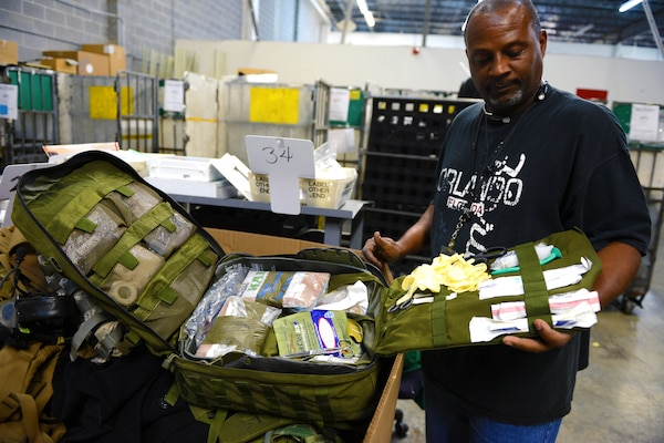 Dyrick Fowler, a clerk in the military section of the U.S. Postal Service's Mail Recovery Center in Atlanta, displays a full medical aid kit contained in one of many crates full of lost military equipment that officials at the center hope to return to the Defense Department, July 11, 2014. The center safeguards military equipment such as night-vision googles, body armor and protective plates in its limited storage space. DoD photo by Army Sgt. 1st Class Tyrone C. Marshall Jr.