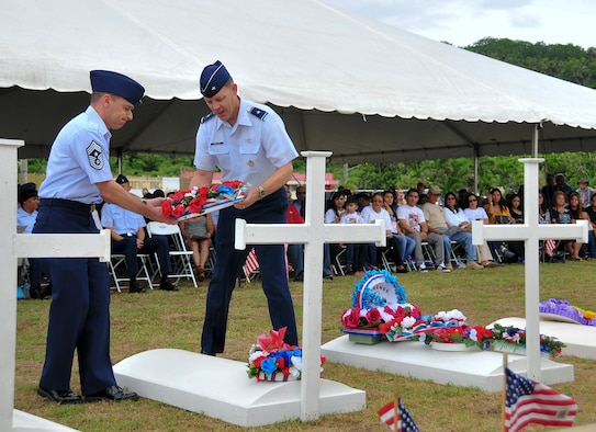 Brig. Gen. Steven Garland, 36th Wing Commander, and Chief Master Sgt. James Slisik, 36th Wing Command Chief, lay a wreath on a grave marker to honor fallen service members who were killed during Operation Enduring Freedom during the Memorial Day Ceremony at the Guam Governor's Complex in Hagåtña, May 26, 2014. Various veterans' organizations laid wreaths on the markers, which were set up to honor veterans who died in conflicts from World War I through Operation Enduring Freedom. (U.S. Air Force Photo by Staff Sgt. Brok McCarthy/Released)