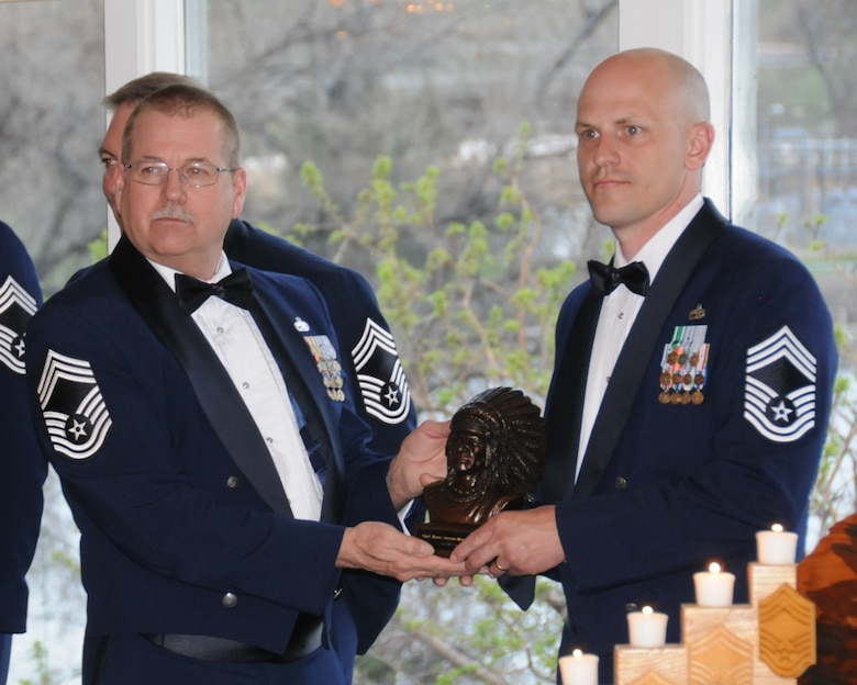 Chief Master Sgt. Steven Lynch, 120th Maintenance Group, presents a wooden bust of an Indian chief to a recently promoted Chief Master Sgt. Brian Furr, 219th RED HORSE, during the chief's induction ceremony May 2 at the Meadow Lark Country Club in Great Falls, Montana.  (National Guard photo/Staff Sgt. Michael Touchette)