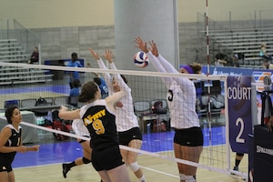 Army CPT Jamie Pecha-#9 (Ft. Bragg, NC) spikes between defenders during the 2014 USA Volleyball National Championships