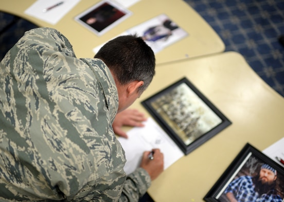 """U.S. Air Force Staff Sgt. Casey Cason, 338th Training Squadron and Baker's Field, Calif., native, bids on an autographed photograph from the members of the T.V. show """"Duck Dynasty"""" during a silent auction in Club Eifel at Spangdahlem Air Base, Germany, May 30, 2014. The base's First Sergeant Council organized this silent auction of nearly 250 memorabilia items to raise money for the Fisher House Foundation, an organization that provides military families a housing option near their service member who was hospitalized for an illness, disease or injury. (U.S. Air Force photo by Staff Sgt. Daryl Knee/Released)"""