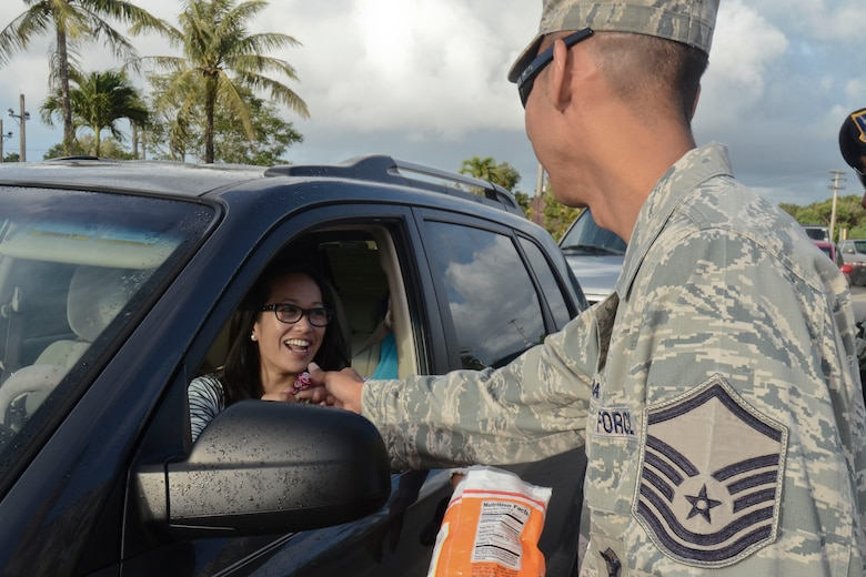 "Master Sgt. Bradley Dapilmoto, 36th Wing Staff Agency first sergeant, hands a piece of candy to a driver entering Andersen Air Force Base, Guam at the main gate May 22, 2014. Base senior leadership handed out candy advertising the Critical Days of Summer 2014 Theme ""Risk:  Double Checks, Not Second Thoughts"".  (U.S. Air Force photo by Airman 1st Class Emily A. Bradley/Released)"