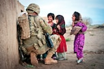 U.S. Army Sgt. Joshua Smith talks to a group of Afghan children during a combined patrol clearing operation in Afghanistan's Ghazni province, April 28, 2012. Smith is assigned to the 82nd Airborne Division's 2nd Battalion, 504th Parachute Infantry Regiment, 1st Brigade Combat Team.