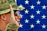The American flag reflects in the glasses of an U.S. Army officer as he reenlists as a paratrooper on Combat Outpost Qara Baugh in Afghanistan's Ghazni province, April 22, 2012. The soldier is assigned to the 82nd Airborne Division's 1st Brigade Combat Team.