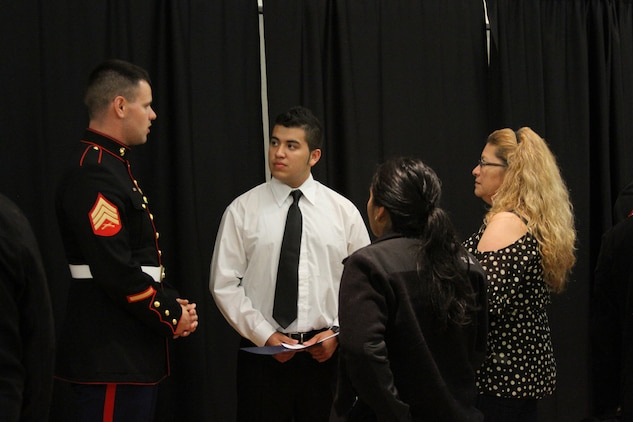 U.S. Marine Corps Sgt. Peter Ballenger, a Westminster, S.C. native and a recruiter with Marine Corps Recruiting Sub-Station Leesburg, speaks to future Marine recruit Ernesto Garcia and his family at the Our Community Salutes' Northern Virginia Chapter recognition ceremony at George Mason University in Fairfax, Va., May 29, 2014. Our Community Salutes' Northern Virginia Chapter is an all-volunteer organization that recognizes young men and women who have chosen to join the military immediately following school graduation. Our Community Salutes started in New Jersey in 2009 and has since spread throughout the country. (U.S. Marine Corps photo by Sgt. Amber Williams/Released)
