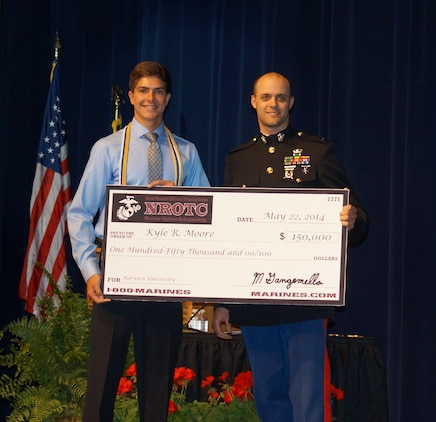 Kyle Moore, a student at Lakeland High School, accepts a $150,000 Naval Reserve Officers Training Corps scholarship presented by U.S. Marine Corps Capt. Michael Gangemella, the executive officer of Recruiting Station Detroit, in front of an auditorium of students, family members and teachers at Lakeland High School May 22, 2014. Moore plans to attend Norwich University in Vermont. Upon completion of his four-year degree in mechanical engineering, Moore will receive his commissioning as a second lieutenant in the U.S. Marines to pursue career opportunities that include pilots, ground combat officers, or a variety of support jobs. (U.S. Marine Corps photo courtesy of Dennis Moore/Released)