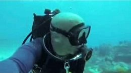 """Former Army diver Mark Claudio """"at home,"""" in scuba gear, drifting along Molasses Reef near Key Largo during a vacation in Florida."""