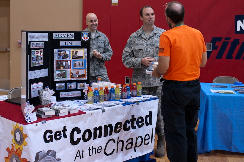 (left to right) 2nd Lt. Daniel Stark, 99th Air Base Wing chaplain candidate, and Staff Sgt. David Day, 99th ABW chaplains assistant, discuss opportunities provided by the chapel with Gregory Valiquette, 88th Test and Evaluation Squadron administrative assistant, during a Health Fair May 30, 2014 at Nellis Air Force Base, Nev.  The chapel provides opportunities for Airmen and their families to strengthen their overall social, physical, mental and spiritual fitness. (U.S. Air Force photo by Senior Airman Timothy Young)