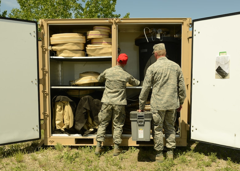 Two 219th RED HORSE Squadron Airmen set up a self-generated water system during a field training exercise at Malmstrom Air Force Base. The water system has the capability to produce 1,500 gallons of drinkable water every hour. (U.S. Air Force photo/Senior Airman Katrina Heikkinen)