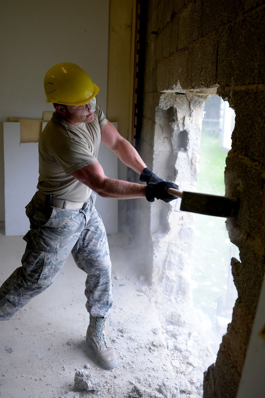 U.S. Air Force Senior Airman Richard Adamson, 52nd Civil Engineer Squadron structures journeyman from Linton, Ind., uses a sledge hammer to create an opening for a doorway in the Skelton Memorial Fitness Center racquet ball courts at Spangdahlem Air Base, Germany, June 3, 2014. The project is part of the remodel of the new combat fitness center which is scheduled to be finished between four and six months. (U.S. Air Force photo by Senior Airman Alexis Siekert/Released)
