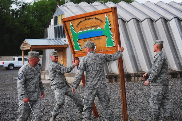 Airmen bring down the iconic sign outside the 376th Air Expeditionary Wing headquarters after the wing's inactivation ceremony June 3, 2014, at Transit Center at Manas, Kyrgyzstan. During its more than 12-year tenure, the wing performed four critical missions including air refueling, onward movement, airlift and humanitarian assistance. (Courtesy photo)
