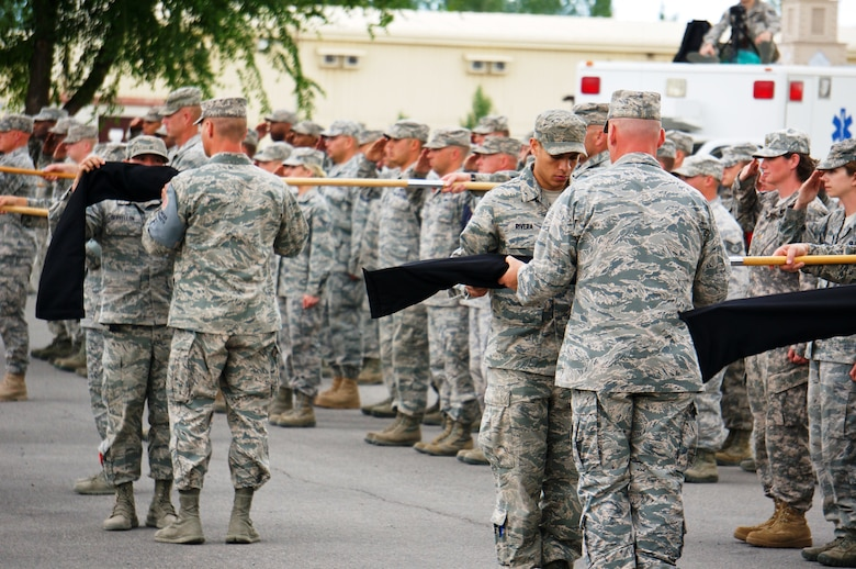 """Airmen sheath squadron guidons as part of the 376th Air Expeditionary Wing inactivation ceremony June 3, 2014, at Transit Center at Manas, Kyrgyzstan. The wing's roots date from the activation of the 376th Bombardment Group during World War II. The 376th AEW took the name """"Liberandos"""" from the B-24 Liberator bombers it flew during this conflict. (Courtesy photo/Capt. Cory O'Brien)"""