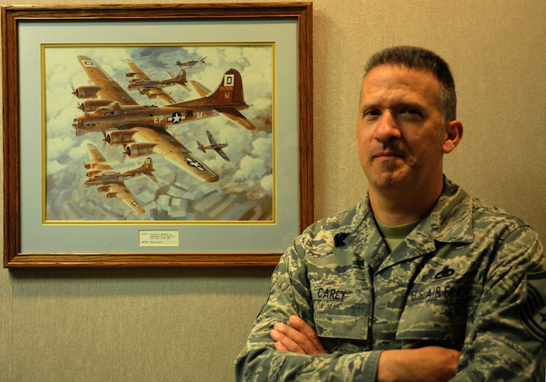 """Master Sgt. Matthew Carey stands by an illustration of several B-17 Flying Fortress bombers on a mission during World War II displayed in the hallway outside his office June 2, 2014, at Ellsworth Air Force Base, S.D. Carey said the image reminds him of his grandfather, B-17 tail gunner Staff Sgt. James """"Rae"""" Carey, and his experiences after he signed in for duty at a base in England one day after the invasion of Normandy began.  Carey is the 28th Bomb Wing Treaty Compliance Office superintendent. (U.S. Air Force photo/Senior Airman Yash Rojas)"""