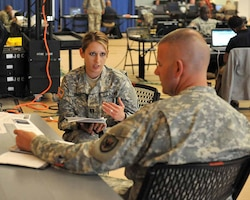 U.S. Army Capt. Angela Erale, public affairs officer, 24th Press Camp Headquarters, prepares U.S. Army Col. Michael Scholes, director of operations, Joint Task Force - Civil Support (JTF-CS), for a press conference during Sudden Response 2014 (SR 14). Members of the Joint Enabling Capabilities Command's Joint Public Affairs Support Element also prepared senior leaders for media engagements during SR 14 by developing talking points. SR 14 tested and validated the unit's movement of equipment and personnel during the initial phases of a simulated man-made or natural disaster.