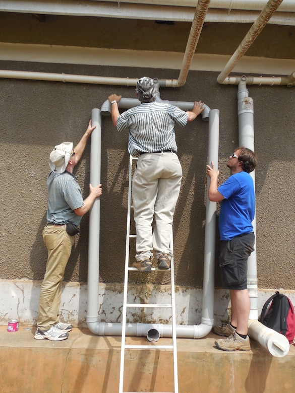 Jim Goedert, EWB-NE Professional; Dwight Hanson EWB-NE-P President ; and Ben Pavlik EWB-NE Student install the modified first flush piping. on St. John's Clinic. The first flush system is a vertical pipe into which the first rainfall from the roof washes at the beginning of a rainfall event. The water from the first flush contains dirt and debris that accumulates on the roof during the dry period. Once the vertical pipe of the first flush system fills; cleaner water flows over it and into the water tanks. The first flush system helps prevent the tanks from filling with dirt and keeps the water in the tank cleaner.