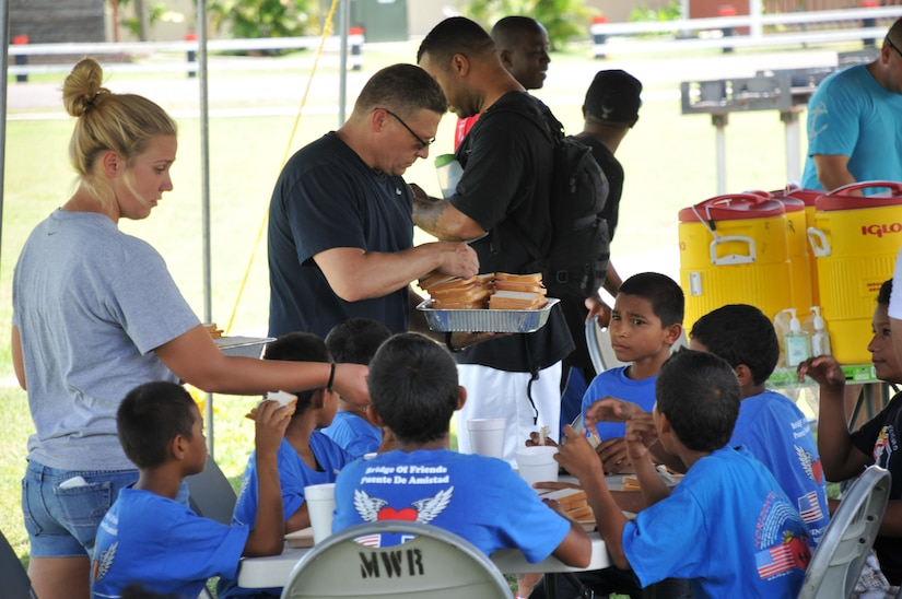U.S. Army Capt. Jeffery Scott, command chaplain, and U.S. Army Spc. Sydney Stankee, along with other servicemembers serve lunch to the kids before taking them to watch a movie. Joint Task Force-Bravo's Army Forces Battalion (ARFOR) hosted a fun-filled Saturday to 45 boys, and five adult chaperones from Horizontes al Futuro orphanage, May 31. The event was an opportunity for many ARFOR members to interact with the boys for the last time before departing Soto Cano. The kids and adults enjoyed a sandwich and chips lunch, as well as playing soccer, and dodge ball with the servicemembers.