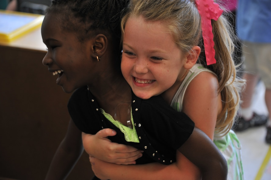 Sarah Caton, right, hugs her best friend Fatou Gueye at the Maxwell Air Force Base child development center, May 20, 2014. Both girls are 4-year-old students at the center. When Fatou, who is from Senegal, first arrived to the CDC she did not speak English, and was not familiar with American customs. Thanks to Sarah Fatou is now fluent in English and comfortable with cultural norms. (U.S. Air Force photo by Staff Sgt. Natasha Stannard)