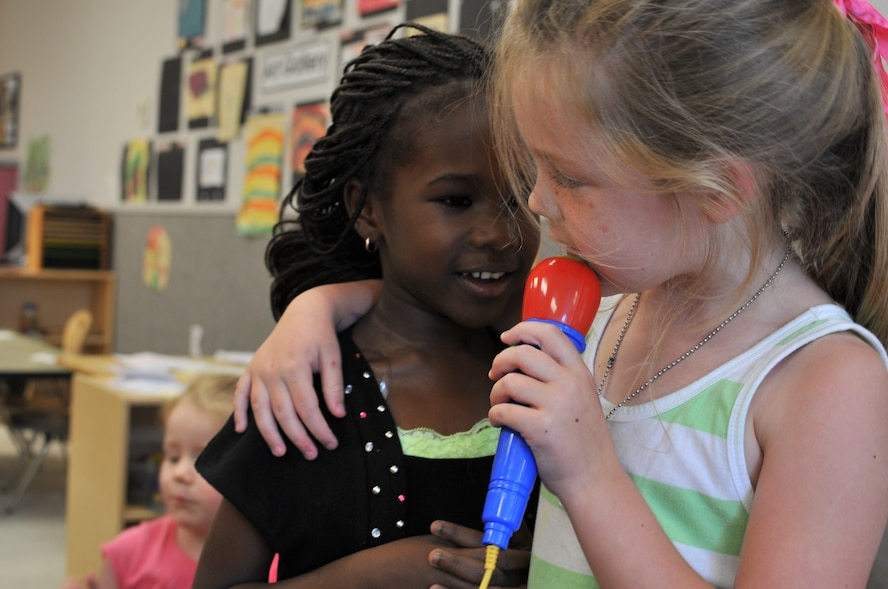 Sarah Caton, a 4-year-old attending the Maxwell Air Force Base child development center, sings to her best friend Fatou Gueye at the CDC, May 20, 2014. Sarah has helped Fatou adjust to American culture since she arrived to the CDC from Senegal in August 2013. (U.S. Air Force photo by Staff Sgt. Natasha Stannard)