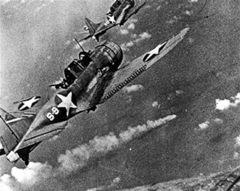 U.S. Navy SBD Dauntless dive bombers approach the burning Japanese heavy cruiser Mikuma for a third round of attacks near Midway Island, June 6, 1942.  Mikuma was one of five Japanese ships destroyed in the Battle of Midway along with approximately 292 Japanese aircraft.  (U.S. Navy photo courtesy of the National Archives Collection)