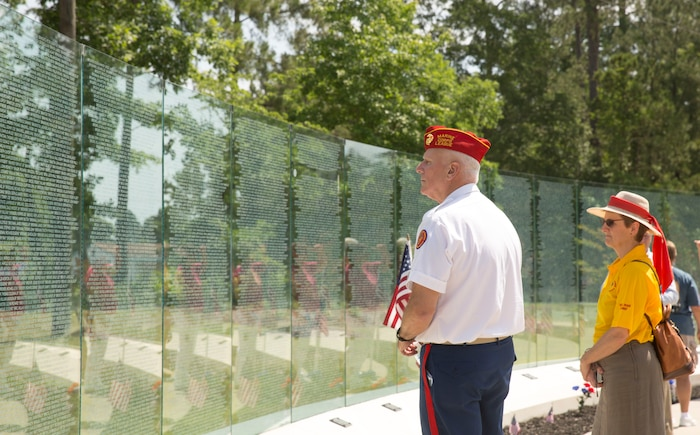 """Michael North, a Vietnam-era Marine veteran, reads the names on the glass walls of the Vietnam Veterans Memorial after a rededications ceremony held for the memorial, at Lejeune Memorial Gardens in Jacksonville, N.C., May 31. North attended the event to reflect on his experiences and to represent his two brothers, who also served but were unable to attend. """"We have always followed the flag,"""" said North, of his family. """"We all feel very deeply about this."""" The ceremony honored the memory of those who perished during the war and celebrated the accomplishments and perseverance of Vietnam-era veterans.(U.S. Marine Corps photo by Cpl. Jackeline M. Perez Rivera/Released)"""