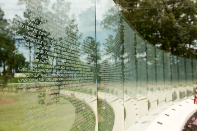 The glass walls at the Vietnam Veterans Memorial at Lejeune Memorial Gardens in Jacksonville, N.C., lists the names of the 58,229 men and women who lost their lives during the Vietnam War. A rededication ceremony was held to commemorate the addition of a gazebo to the memorial, May 31. The ceremony honored the memory of those who perished during the war and celebrated the accomplishments and perseverance of Vietnam-era veterans.(U.S. Marine Corps photo by Cpl. Jackeline M. Perez Rivera/Released)