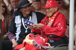 Chester Nez, the last surviving Navajo code talker from Platoon 382, holds an American flag that was handed to him by Pfc. Tiffany Boyd, data network specialist, at Code Talkers Hall on April 4, 2014. Nez passed away June 4, 2014.
