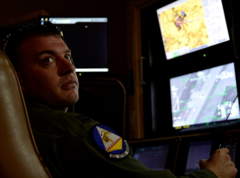 Capt. Andrew, 18th Reconnaissance Squadron pilot, flies a remotely piloted aircraft using a flight training simulator May 28, 2014, after flying the 65th combat air patrol, which launched earlier that morning. Andrew was selected to fly the 65th CAP, an initiative set by then Secretary of Defense Robert Gates Dec. 23, 2009 (Last names have been withheld for security purposes). (U.S. Air Force photo by Staff Sgt. Adawn Kelsey/Released)