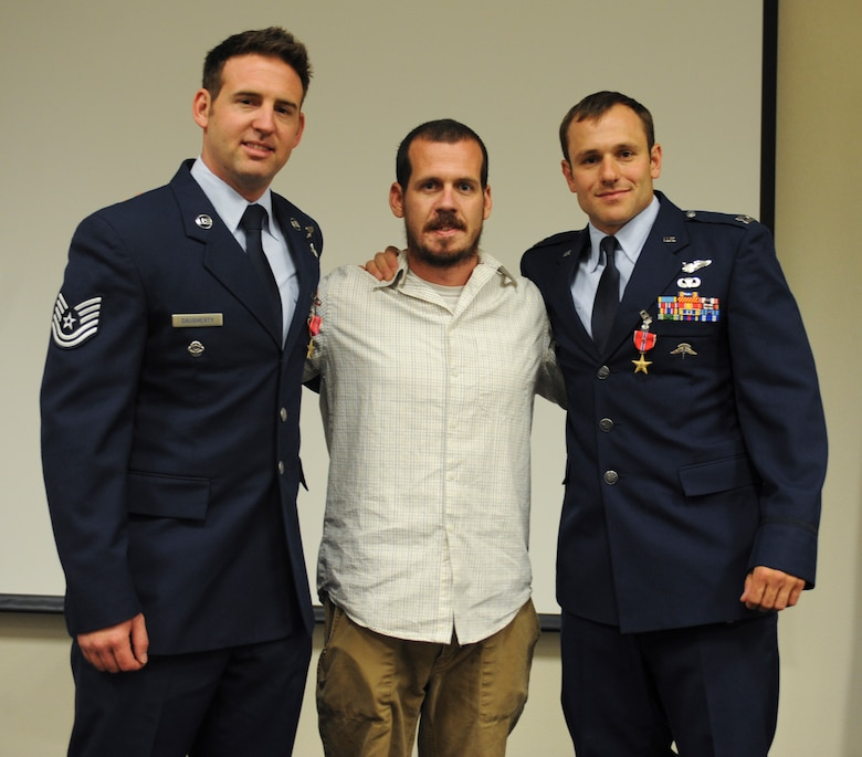 U.S. Air Force Capt. Kevin Epstein, 48th Rescue Squadron combat rescue officer, Tech. Sgt. Brandon Daugherty, 306th Rescue Squadron pararescueman, and U.S. Marine Corps retired  Michael Stringer, explosive ordnance technician, pose for a photo during a Bronze Star Medal presentation ceremony at Davis-Monthan Air Force Base, Ariz., June 2, 2014. Epstein and Daugherty risked their lives in order to save Stringer's life while deployed to Afghanistan. (U.S. Air Force photo by Senior Airman Sivan Veazie/Released)
