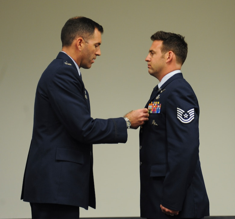 U.S. Air Force Tech. Sgt. Brandon Daugherty, 306th Rescue Squadron pararescueman, receives a Bronze Star Medal with valor from Col. Sean Choquette, 563rd Rescue Group commander, at Davis-Monthan Air Force Base, Ariz., June 2, 2014. Daugherty distinguished himself by heroism as pararescue team leader for the 46th Expeditionary Rescue Squadron, 651st Air Expeditionary Group, 451st Air Expeditionary Wing while engaged in action against an enemy forces in Afghanistan on  Feb. 21, 2012. (U.S. Air Force photo by Senior Airman Sivan Veazie/Released)