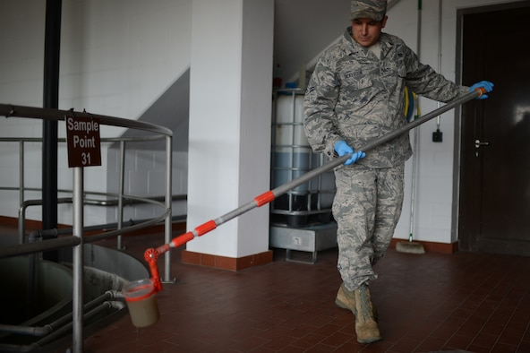 U.S. Air Force Airman 1st Class Joseph Dickerson, 52nd Civil Engineer Squadron water and fuel system maintenance technician from Oklahoma City, Okla., takes a water sample from a tank of wastewater at Spangdahlem Air Base, Germany, June 4, 2014. The water treatment facility can process approximately 2,000 cubic meters of wastewater from the base per day. (U.S. Air Force photo by Senior Airman Gustavo Castillo/Released)