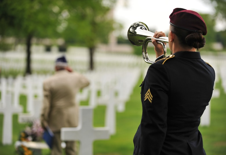 Leslie Cruise, a World War II veteran, salutes the grave of Pvt. Richard Vargas while Army Sgt. Jeannette Mason, 5th Quartermaster Theater Aerial Delivery Company parachute rigger, plays taps during a wreath laying ceremony at Lorraine American National Cemetery and Memorial, St. Avold, France, June 2, 2014. Seventy years ago on June 7, 1944 Pvt. Richard Vargas saved Cruise's life during the invasion of Normandy. Cruise went to France several times prior to this visit looking for his friend's grave in order to say thank you. (U.S. Air Force photo/Senior Airman Hailey Haux)