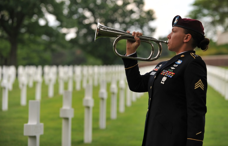 Army Sgt. Jeannette Mason, 5th Quartermaster Theater Aerial Delivery Company parachute rigger, plays taps during a wreath laying ceremony at Lorraine American National Cemetery and Memorial, St. Avold, France, June 2, 2014. Seventy years ago on June 7, 1944 Pvt. Richard Vargas saved Leslie Cruise's life, a World War II veteran, during the invasion of Normandy. Cruise went to France several times prior to this visit looking for his friend's grave in order to say thank you. (U.S. Air Force photo/Senior Airman Hailey Haux)