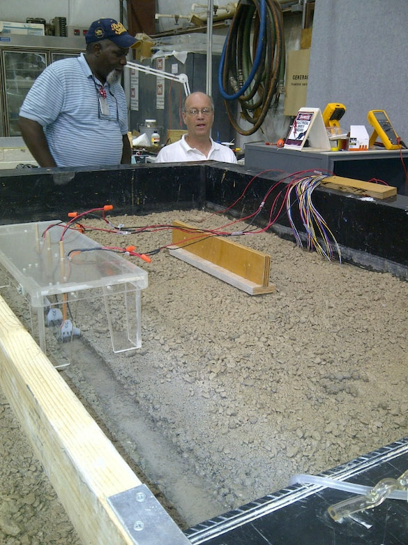 "Mr. Richard Hudson, left, and Dr. David Gent, right, discuss the 1:1000 scale model of the Chicago Canal system in the HWRC ""pit"" area that is used to observe the potential corrosion-related effects of the electrical fish barriers in the canal and evaluate a mitigation approach for use in the canal."