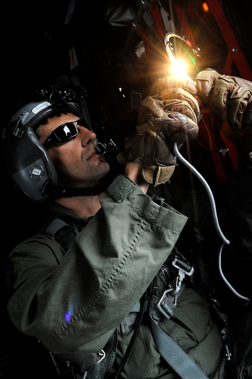 Tech. Sgt. Andy Strause signals to nearby aircraft May 7, 2014, while on a joint refueling training mission out of Kadena Air Base, Japan. During the mission, the MC-130P Combat Shadow crew from the 17th Special Operations Squadron refueled two helicopters and performed essential pilot training. (U.S. Air Force photo/Senior Airman Maeson L.Elleman)