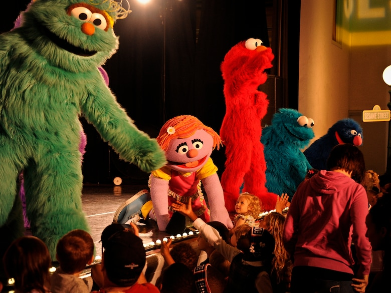 Katie, a Sesame Street character, reaches out to children in the audience during a performance May 28, 2014, at Joint Base McGuire-Dix-Lakehurst, N.J. The show was designed to shine a light on difficult situations a military child may face while allowing parents the opportunity to address stressful situations that may arise while serving in the armed forces. (U.S. Air Force photo/Staff Sgt. Scott Saldukas)
