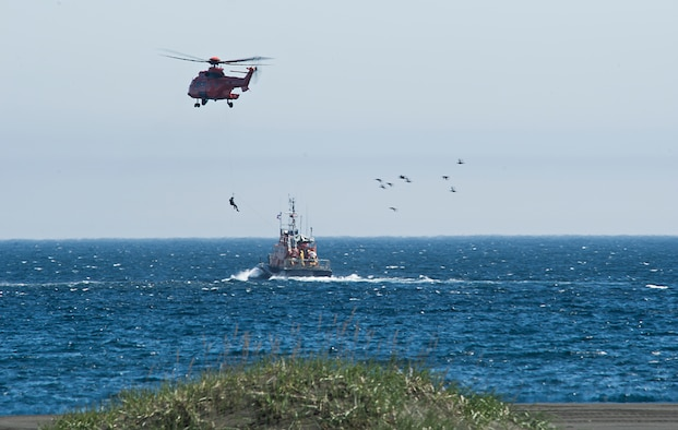 A U.S. Air Force pararescueman descends from an Icelandic Super Puma during a ceremony May 30, 2014, commemorating a rescue mission on the coastline of Voldlavik, Iceland. During the mission, U.S. Airmen saved the lives of six Icelanders stranded aboard their ship.. (U.S. Air Force photo/Tech. Sgt. Benjamin Wilson)